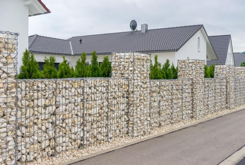 Ein moderner Garten mit einem Gabionenzaun umrandet